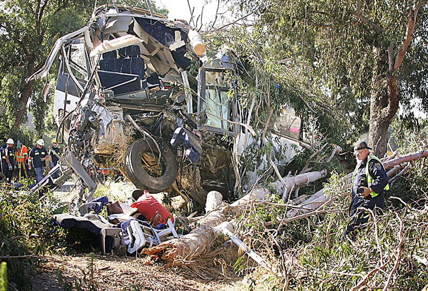A CHP officer investigates a Greyhound Bus crash that killed at least six people and injured many others on Thursday, July 22, 2010, in Fresno, Calif. (AP Photo/Gary Kazanjian)