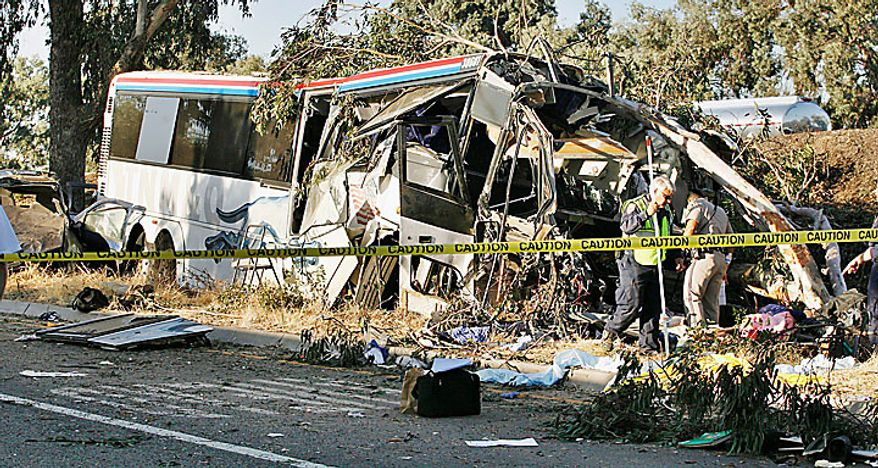 California Highway Patrol officers investigate a Greyhound bus crash on Highway 99 in Fresno, Calif., that killed at least six people and injured many others on Thursday, July 22, 2010. (AP Photo/Gary Kazanjian)