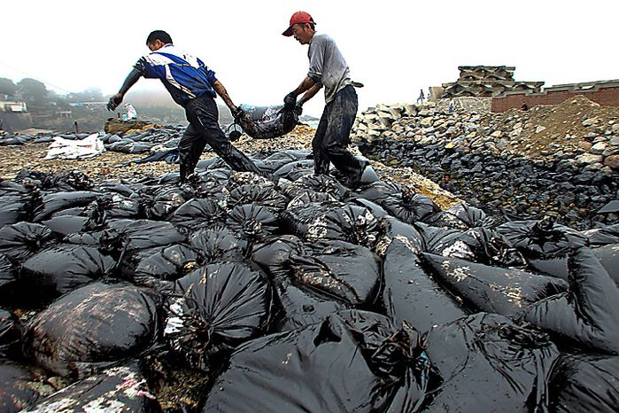 In this photo taken Wednesday, July 21, 2010, workers move a bag on the beach polluted by crude oil after a pipeline explosion in Dalian in northeast China's Liaoning province. China National Petroleum Corp. said Thursday a vital
