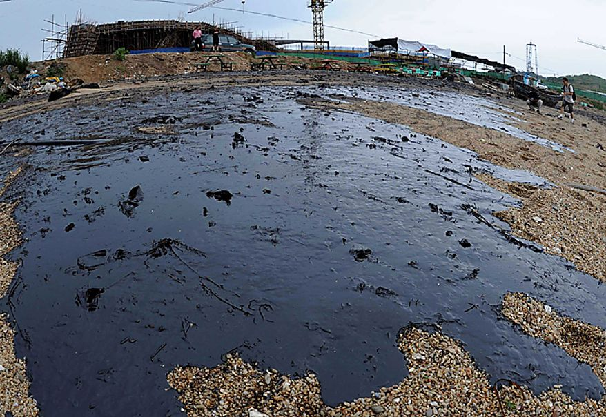 In this Tuesday, July 20, 2010 photo, the surface of a beach is covered by the spilled crude oil in Dalian, a coastal city in northeast China's Liaoning province. The oil had spread over water since a pipeline at the busy northeastern port exploded, hurting oil shipments from part of China's strategic oil reserves to the rest of the country.  (AP Photo/Xinhua, Li Gang)