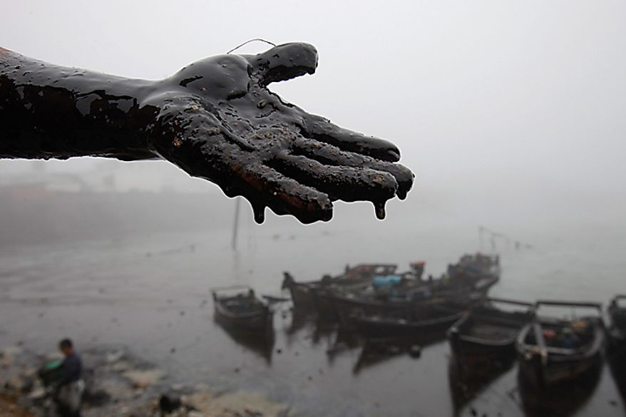 In this photo taken on Wednesday, July 21, 2010, and released by Greenpeace, a villager displays his hand coated in crude oil during cleanup efforts almost a week after a pipeline, owned by China Nation Petroleum Corp., exploded in Nanhaitun, Weitang Bay, China. China National Petroleum Corp. said Thursday the vital pipeline has resumed operations after an explosion caused the country's largest reported oil spill. Cleanup efforts, marred by the drowning death of a worker, continued over 165 square mile stretch of water blanketed in thick, dark oil Thursday, after an official warned the spill posed a severe threat to sea life and water quality. (AP Photo/Greenpeace, Jiang He)