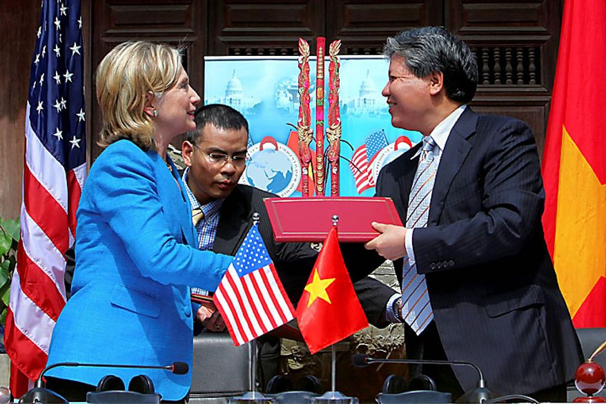 U.S. Secretary of State Hillary Rodham Clinton, left, and Vietnam Minister of Justice Ha Hung Cuong exchange memorandum of understanding for U.S. support of HIV/AIDS programs at Ngoc Lam Pagoda in Hanoi, Vietnam, Thursday, July 22, 2010. (AP Photo/Julian Abram Wainwright, Pool)