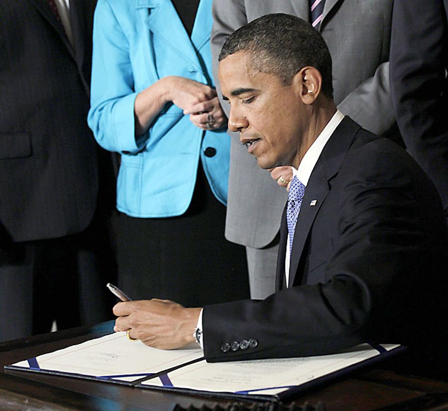 President Obama signs the Improper Payments Elimination and Recovery Act in a ceremony in the State Dining Room of the White House in Washington on Thursday, July 22, 2010. (AP Photo/Pablo Martinez Monsivais)