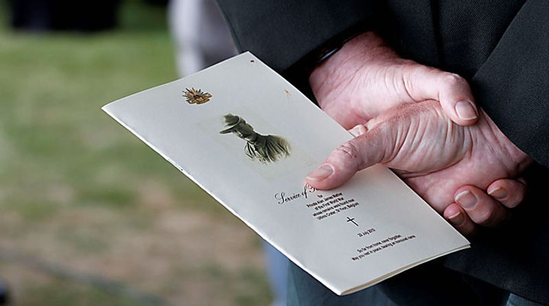 A man holds the funeral program of Australian World War One soldier, Private Alan James Mather during a re-burial ceremony at Prowse Point Cemetery in Ploegsteert, Belgium on Thursday, July 22, 2010. Mr. Mather, originally from Invernell, NSW, Australia was one of 216,000 men from Australia, New Zealand and the UK who fought in the Battle of Messines from June 7-14, 1917. The body of Mr. Mather was discovered by a British archeological team in 2008 and further DNA tests by a Belgian laboratory revealed his full identity. (AP Photo/Virginia Mayo)