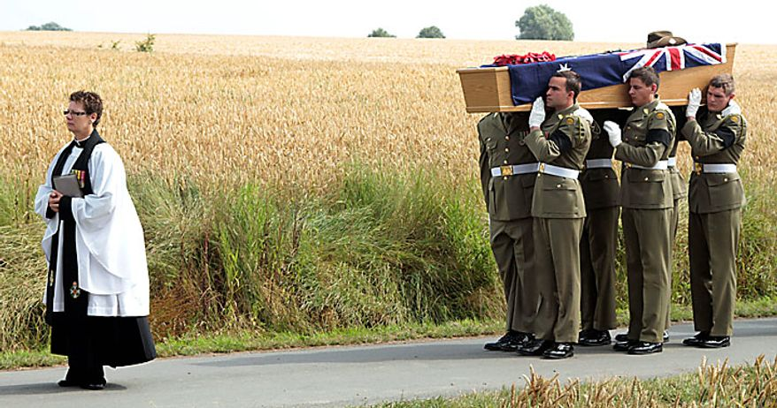 Members of the Australian Federation Guard carry the coffin of Australian WWI soldier, Private Alan James Mather, during a re-burial ceremony at Prowse Point Cemetery in Ploegsteert, Belgium on Thursday, July 22, 2010. The body of Mr. Mather was discovered by a British archeological team in 2008, and further DNA tests by a Belgian laboratory revealed his full identity. (AP Photo/Matthew Busch)