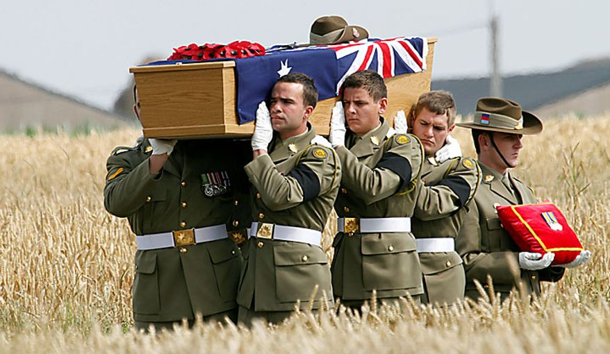 Members of the Australian Federation Guard carry the coffin of Australian WWI soldier, Private Alan James Mather, during a re-burial ceremony at Prowse Point Cemetery in Ploegsteert, Belgium, on Thursday, July 22, 2010. Mr. Mather's body was discovered by a British archeological team in 2008, and further DNA tests by a Belgian laboratory revealed his full identity. (AP Photo/Virginia Mayo)