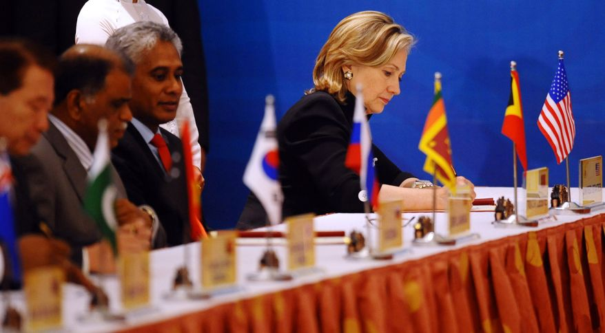 U.S. Secretary of State Hillary Rodham Clinton, right, signs the Treaty of Amity and Cooperation along with others at the end of the 17th ASEAN Regional Forum (ARF), in Hanoi, Vietnam, Friday, July 23, 2010. (AP Photo/Hoang Dinh Nam, Pool)