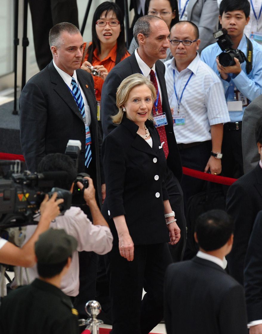 U.S. Secretary of State Hillary Rodham Clinton, center, arrives to attend the opening of the ASEAN Regional Forum on Friday July 23, 2010, in Hanoi. The forum is attended by foreign ministers from the Association of Southeast Asian Nations (ASEAN) and their counterparts from partners countries including U.S., China, Russia, Japan and South Korea. (AP Photo/HOANG DINH Nam, Pool)