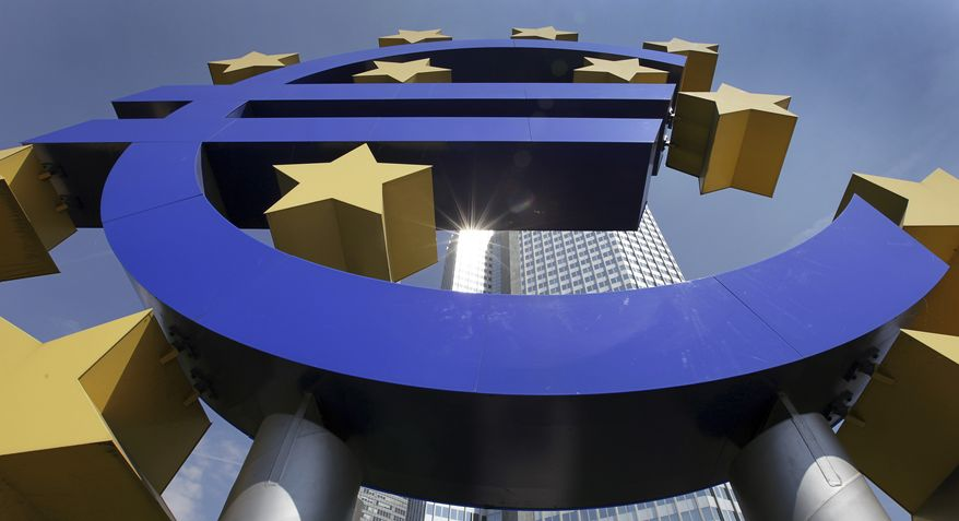 The sun is reflected on the facade of the European Central Bank Tower, seen through the euro symbol, in Frankfurt, Germany, in August 2009. (AP Photo/Daniel Roland, File)