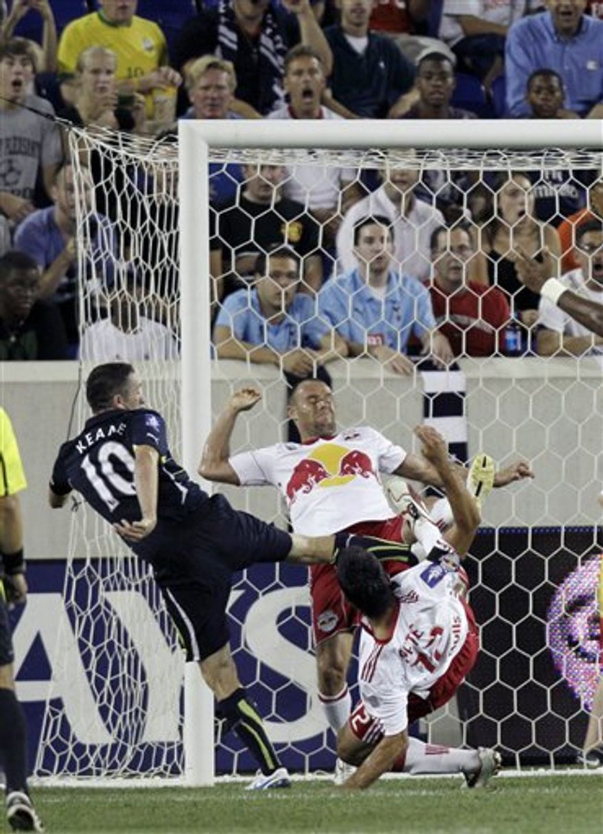 Tottenham's Robbie Keane (10) takes a shot on goal between New York Red Bulls' Joel Lindpere, center, and Mike Petke, right, during the second half of an exhibition soccer match Thursday, July 22, 2010, in Harrison, N.J. Tottenham won 2-1. (AP Photo/ Mel Evans)