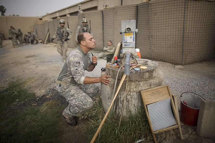 A U.S. Army soldier belonging to the 1-320th Alpha Battery, 2nd Brigade of the 101st Airborne Division, has an early morning shave by a well at COP Nolen, in the volatile Arghandab Valley, Kandahar, Afghanistan, Friday, July 23, 2010. (AP Photo/Rodrigo Abd)