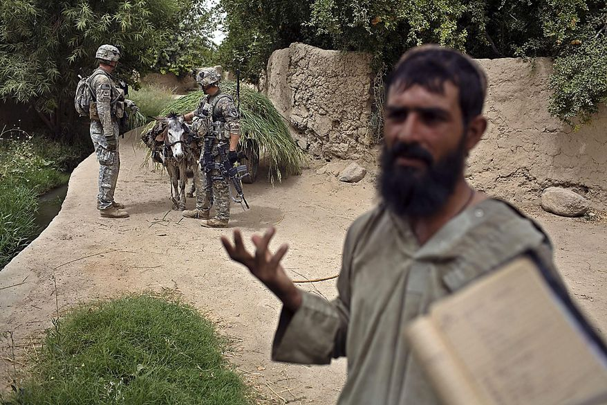 An Afghan farmer is questioned as U.S. Army soldiers of the 1-320th Alpha Battery, 2nd Brigade of the 101st Airborne Division search his cart for hidden weapons and bombs near COP Nolen, in the volatile Arghandab Valley, Kandahar, Afghanistan, Friday, July 23, 2010. (AP Photo/Rodrigo Abd)