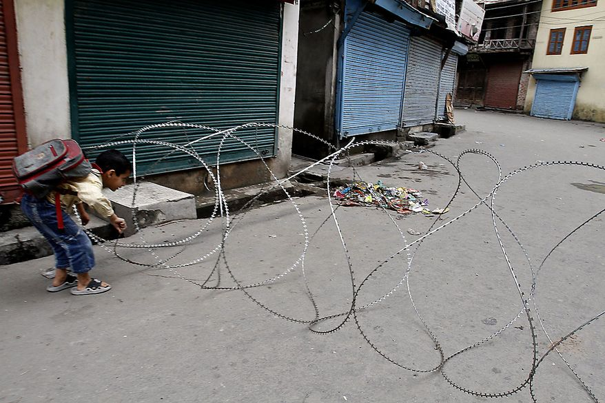 A Kashmiri boy tries to cross barbed wire set-up by Indian police as a barricade on a deserted street in Srinagar, India, Friday, July 23, 2010. The predominantly Muslim region, where resistance to rule by Hindu-majority India is strong, has witnessed curfews and strikes for nearly a month after anti-India street protests and clashes surged. Residents accuse government forces of killing at least 17 people, mostly teenagers, in the demonstrations. (AP Photo/Mukhtar Khan)