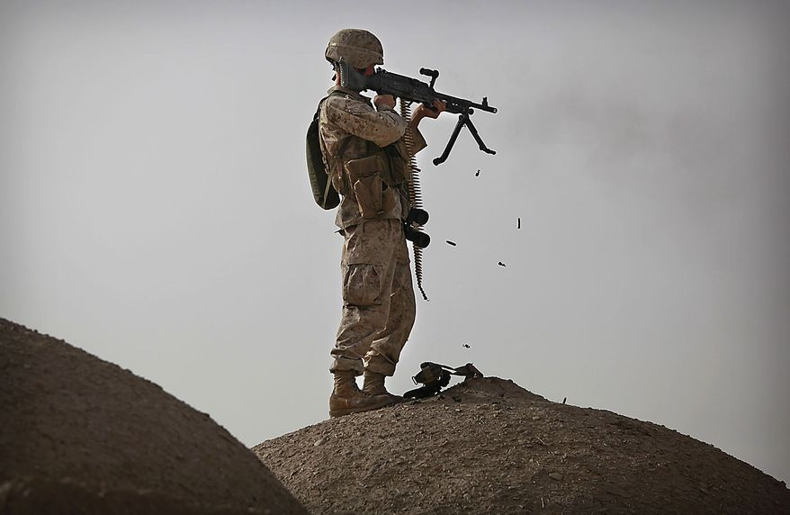 United States Marine Cpl. Jesse Hopkins from Bravo Company of the 1st Battalion of the 2nd Marines fires a machine gun during a gunbattle as part of an operation to clear the area of insurgents near Musa Qaleh, in northern Helmand Province, southern Afghanistan, Friday, July 23, 2010. (AP Photo/Kevin Frayer)