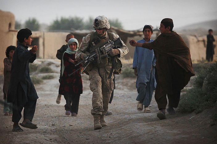 A United States Marine from Bravo Company of the 1st Battalion of the 2nd Marines is surrounded by Afghan locals during an operation to clear the area of insurgents near Musa Qaleh, in northern Helmand Province, southern Afghanistan, Friday, July 23, 2010. (AP Photo/Kevin Frayer)