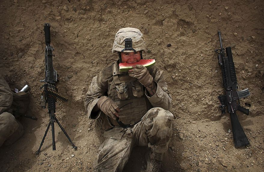 A United States Marine from Bravo Company of the 1st Battalion of the 2nd Marines eats watermelon as he rests following a gunbattle as part of an operation to clear the area of insurgents near Musa Qaleh, in northern Helmand Province, southern Afghanistan, Friday, July 23, 2010. (AP Photo/Kevin Frayer)