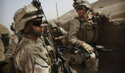 United States Marine Lt. Benny Rhodes, right, from Bravo Company of the 1st Battalion of the 2nd Marines leads operations during a gunbattle as part of an operation to clear the area of insurgents near Musa Qaleh, in northern Helmand Province, southern Afghanistan, Friday, July 23, 2010. (AP Photo/Kevin Frayer)