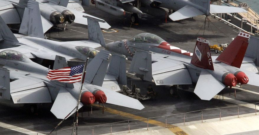 """A U.S. navy personnel takes a rest under the wings of a fighter jet plane on the deck of U.S. nuclear-powered aircraft carrier USS George Washington at the Busan port in Busan, south of Seoul, South Korea, Saturday, July 24, 2010. North Korea warned Saturday that joint U.S. and South Korean military exercises poised to begin this weekend amount to a military provocation that will draw a """"powerful"""" nuclear response from Pyongyang. (AP Photo/Lee Jin-man)"""