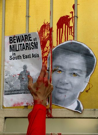 An Indonesian activist puts a poster next to a mask of Mr. Abhisit on the gate of the Thai Embassy during a protest against the military crackdown against Red Shirts in Bangkok. (Associated Press)