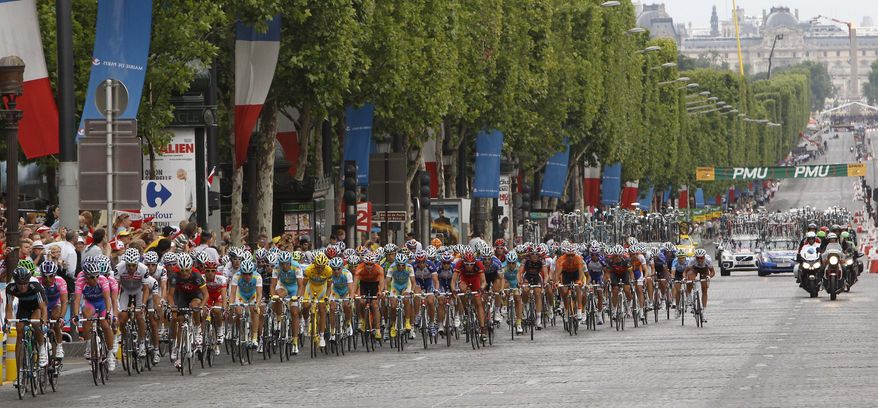 The pack -- including Alberto Contador of Spain, wearing the overall leader's yellow jersey -- cycles up the Champs-Elysees in Paris during the 20th and last stage of the Tour de France cycling race on Sunday, July 25, 2010. (AP Photo/Christophe Ena)