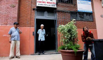 Men stand in front of Kwong Wah Po in Havana's Chinatown. The paper contains articles mostly translated from the state-run media, but does have a few freedoms. (Associated Press)
