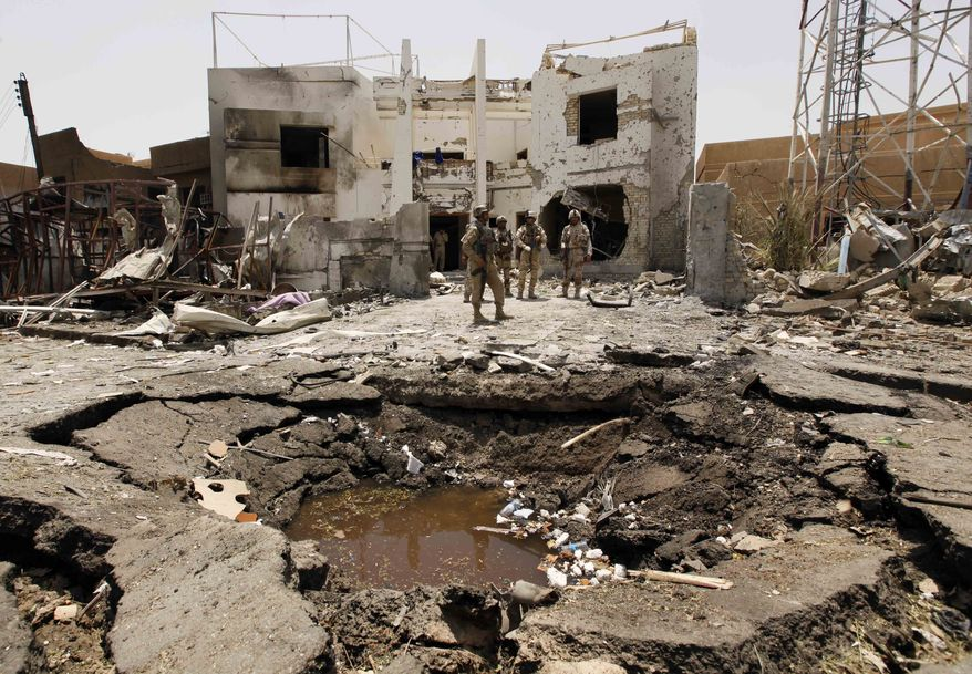 Iraqi army soldiers stand near a massive crater outside the office of the Al-Arabiya television channel after a suicide bomber driving a minibus struck in Baghdad on Monday, July 26, 2010. (AP Photo/Hadi Mizban)
