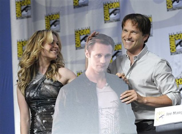 "Actor Stephen Moyer, right, and actress Anna Paquin, left, hold up a cardboard cutout of actor Alexander Skarsgard at a panel discussion of their cable television series ""True Blood"" at Comic Con in San Diego, Calif. on Friday, July 23, 2010. (AP Photo/Dan Steinberg)"
