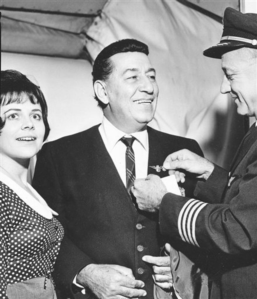 FILE - In this Sept. 3, 1965 file photo, jazz musician Louis Prima, center, accompanied by his wife Gia, left, receives a pin from a TWA crew member on the occasion of his first plane ride in New York City.  The late 'King of Swing' Louis Prima has received the 2,413th star on the Hollywood Walk of Fame in a centennial celebration that included dancing in the street to his big-band sounds. The influential band leader was honored at a Sunday, July 25, 2010 ceremony on Vine Street attended by his son Louis Prima Jr., who continues the legacy of his father's music, his daughter Lena Prima, celebrities, dignitaries and fans. (AP Photo, File)