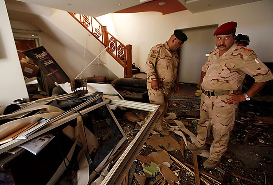 Iraqi army soldiers stand in the ruins of the office of the Al-Arabiya television station after a suicide bomber driving a minibus struck in Baghdad, Iraq, Monday, July 26, 2010. The bomber was apparently waved through the first checkpoint at the Al-Arabiya television station after security guards checked his identification, said Iraqi military spokesman Maj. Gen. Qassim al-Moussawi. The blast killed and injured several people at the popular Arabic-language satellite news channel early Monday. (AP Photo/Hadi Mizban)
