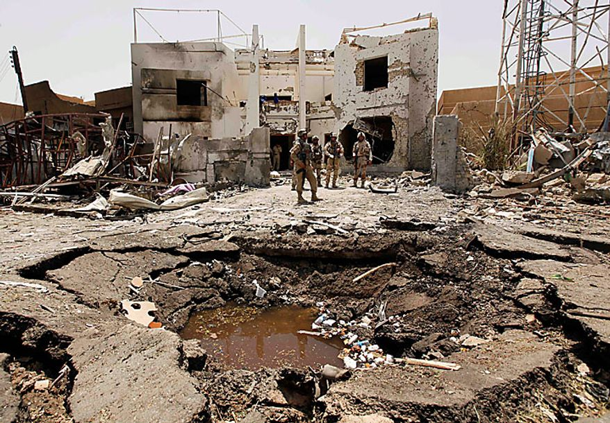 Iraqi army soldiers stand near a massive crater outside the office of the Al-Arabiya television station after a suicide bomber driving a minibus struck in Baghdad, Iraq, Monday, July 26, 2010. The bomber was apparently waved through the first checkpoint at the Al-Arabiya television station after security guards checked his identification, said Iraqi military spokesman Maj. Gen. Qassim al-Moussawi. The blast killed and injured several people at the popular Arabic-language satellite news channel early Monday. (AP Photo/Hadi Mizban)