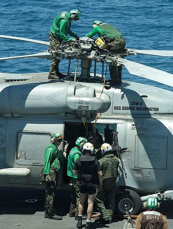 Deck crew members check a helicopter on the flight deck of the Nimitz-class USS George Washington for joint military exercises between the U.S. and South Korea in South Korea's East Sea on Monday, July 26, 2010. U.S. and South Korean warships and helicopters practiced anti-submarine maneuvers off the Korean Peninsula Monday that officers sa