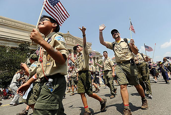 Scouts and Scout leaders wave to the reviewing stand during the Boy Scout Association Grand Centennial Parade along Constitution Avenue in Washin
