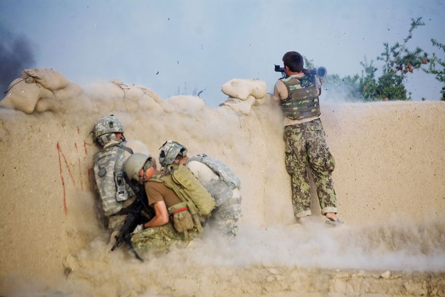 HELP ON THE WAY: An Afghan soldier fighting alongside U.S. troops launches a grenade during a clash in Kandahar. President Obama will get a $59 billion emergency war-spending bill to sign to fund his U.S. troop surge. (Associated Press)