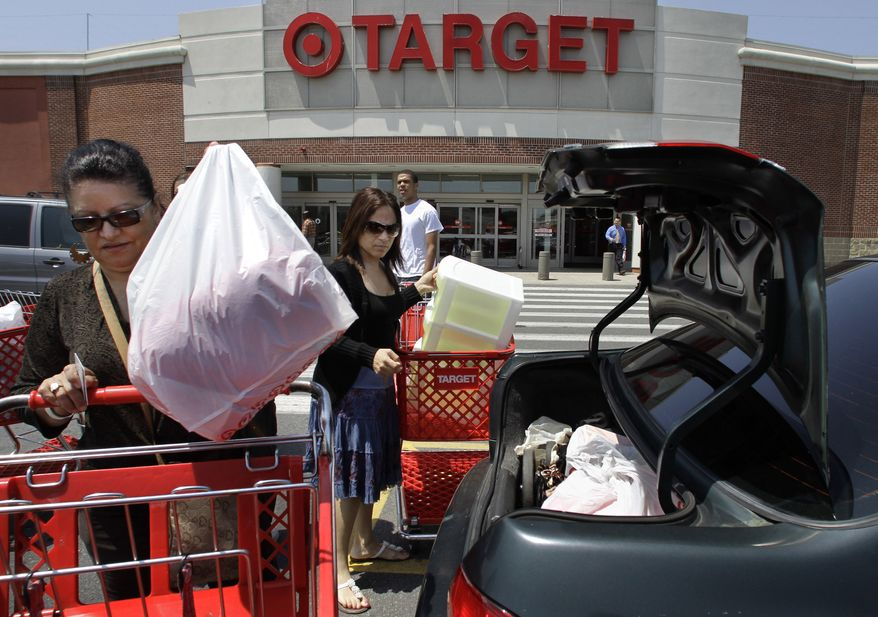 ** FILE ** Shoppers Joselin Pena (left) and niece Ingrid Romero (center), both of Boston, load packages into their car after shopping at a Target store in Boston in early June. (AP Photo/Steven Senne, file)