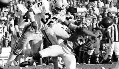 """FILE-This Jan. 9, 1977 file photo shows Minnesota Vikings wide receiver Sammy White losing his helmet as two Oakland Raiders hit him in the Super Bowl XI game at Pasadena, Calif. Raiders are, defensive backs Jack Tatum (32) and Skip Thomas. Tatum, the All-Pro safety for the Oakland Raiders best known for his hit that paralyzed Darryl Stingley in an NFL preseason game in 1978, has died. He was 61.  Nicknamed """"The Assassin,"""" Tatum died of a heart attack Tuesday July 27, 2010 in Oakland, according to friend and former Ohio State teammate John Hicks. (AP Photo/Richard Drew,File)"""