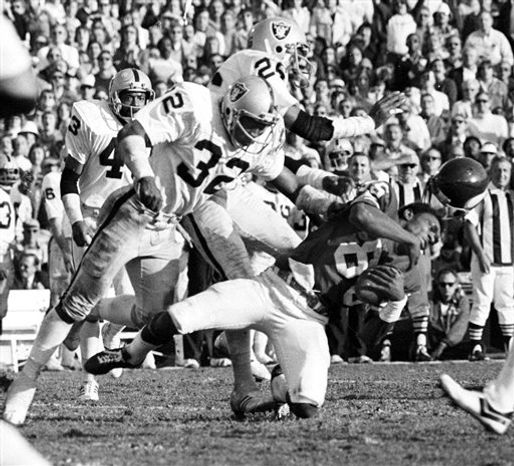"FILE-This Jan. 9, 1977 file photo shows Minnesota Vikings wide receiver Sammy White losing his helmet as two Oakland Raiders hit him in the Super Bowl XI game at Pasadena, Calif. Raiders are, defensive backs Jack Tatum (32) and Skip Thomas. Tatum, the All-Pro safety for the Oakland Raiders best known for his hit that paralyzed Darryl Stingley in an NFL preseason game in 1978, has died. He was 61.  Nicknamed ""The Assassin,"" Tatum died of a heart attack Tuesday July 27, 2010 in Oakland, according to friend and former Ohio State teammate John Hicks. (AP Photo/Richard Drew,File)"