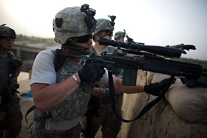US Army soldiers of the 1-320th Alpha Battery, 2nd Brigade of the 101st Airborne Division, over-watch insurgent positions during clashes at COP Nolen, in the volatile Arghandab Valley, Kandahar, Afghanistan, Tuesday, July 27, 2010. (AP Photo/Rodrigo Abd)
