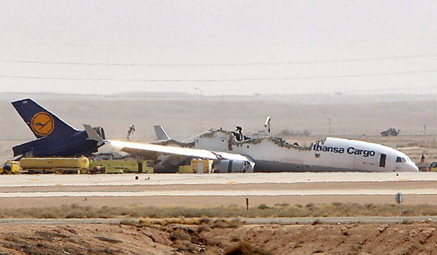 A man stands on top of the wreckage of a Lufthansa cargo plane that caught fire and split in half as it was landing in Riyadh, Saudi Arabia, on Tuesday, July 27, 2010. The German pilot and co-pilot of Flight 8460, which was carrying about 90 tons of unspecified cargo, were slightly injured, an airport official said. (AP Photo)
