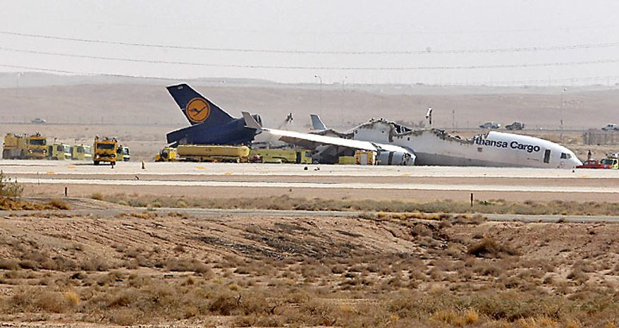 Fire engines (far left) line up behind the wreckage of a Lufthansa cargo plane that caught fire and split in half as it was landing in Riyadh, Saudi Arabia, on Tuesday, July 27, 2010. The German pilot and co-pilot of Flight 8460, which was carrying about 90 tons of unspecified cargo, were slightly injured, an airport official said. (AP Photo)