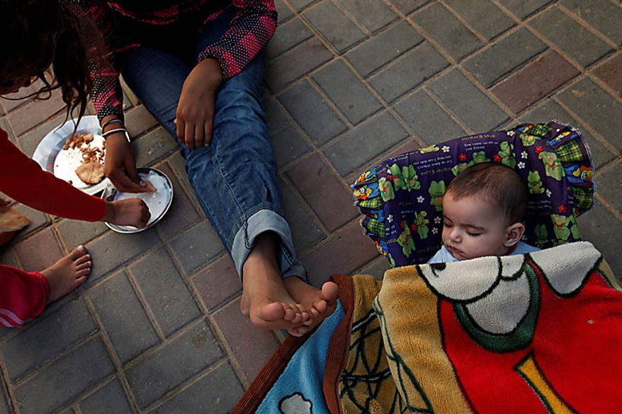 Five month-old Palestinian girl Leyali Awaja sleeps in the makeshift structures that house her family as her siblings Omsyat and Hala eat their lunch, in Beit Lahiya, northern Gaza Strip, Thursday June 10, 2010. The Awajas are among thousands of families whose houses were destroyed during Israel's three-week military offensive against Hamas-ruled Gaza, launched in December 2008 with the aim of halting Hamas rocket attacks. An Israeli forces bulldozer flattened the Awajas' house and as the family tried to flee, bullets hit Leyali's father Kamal, mother Wafa, and 8-year-old brother Ibrahim, who bled to death in the street. (AP Photo/Lefteris Pitarakis)