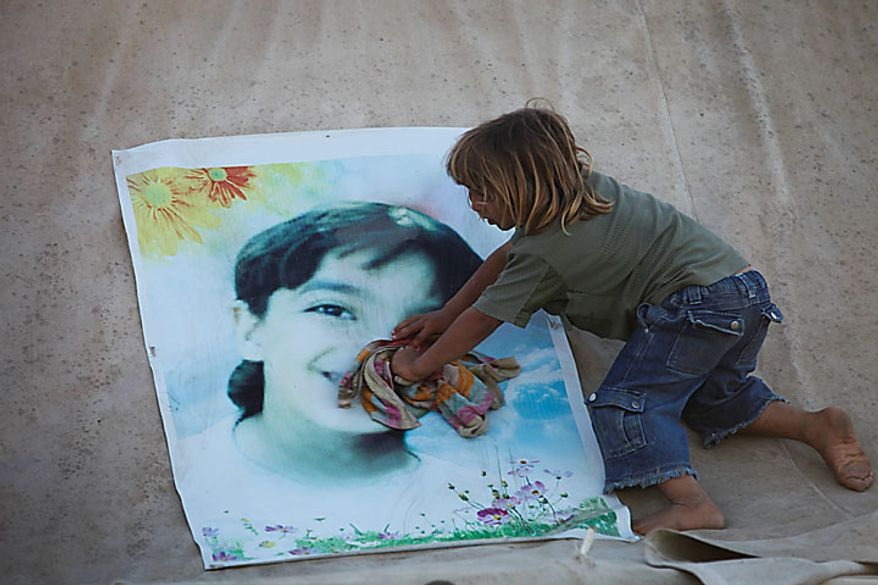 Palestinian Dia Awaja, 4, cleans a portrait of his late brother Ibrahim, killed during an Israeli army operation, atop a tent that makes up part of the makeshift structures that house the family in Beit Lahiya, northern Gaza Strip, Thursday, June 10, 2010. The Awajas are among thousands of families whose houses were destroyed during Israel's three-week military offensive against Hamas-ruled Gaza, launched in December 2008 with the aim of halting Hamas rocket attacks. An Israeli forces bulldozer flattened the Awajas' house and as the family tried to flee, bullets hit father Kamal, mother Wafa, and 8-year-old son Ibrahim, who bled to death in the street. (AP Photo/Lefteris Pitarakis)