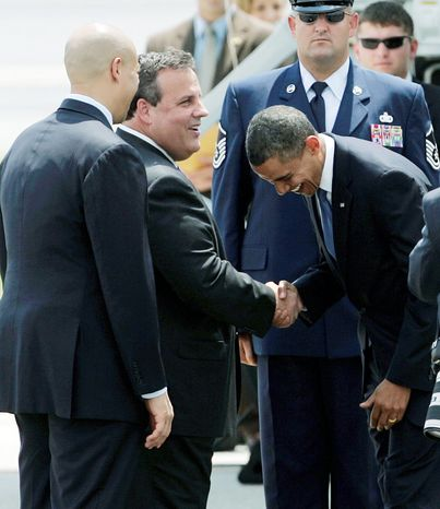 Associated Press President Obama laughs as he's welcomed by a bipartisan duo - New Jersey Gov. Chris Christie (center), a Republican, and Newark Mayor Cory Booker, a Democrat - upon his arrival aboard Air Force One in Newark, N.J.