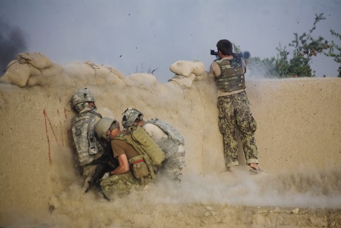 An Afghan soldier launches a rocket-propelled grenade as U.S. soldiers of the 1-320th Alpha Battery, 2nd Brigade, of the 101st Airborne Division duck during a clash with insurgents at in the volatile Arghandab Valley in Kandahar, Afghanistan, on Tuesday, July 27, 2010. (AP Photo/Rodrigo Abd)