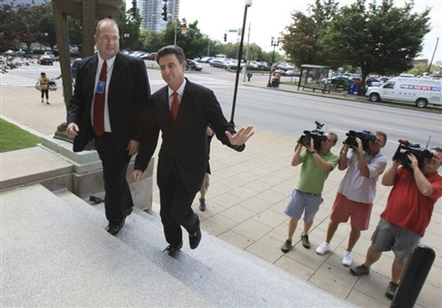 A representative from the US Attorney's Office escorts University of Louisville basketball coach Rick Pitino, second left, to the federal courthouse in Louisvile Wednesday, July 28, 2010.  Pitino will testify in the trial of Karen Sypher who is accused of attempting to extort money from the coach after a sexual encounter.  (AP Photo/ The Courier-Journal, Barry Westerman)  NO MAGS NO SALES NO ARCHIVES