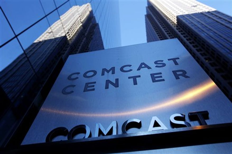 Comcast logos are displayed on installation trucks in Pittsburgh, Tuesday, Feb. 15, 2011. Comcast Corp., a leading cable, entertainment and communications company, announced Wednesday, Feb. 16, that the company's planned annual dividend has increased 19% to $0.45 per share.  (AP Photo/Gene J. Puskar)
