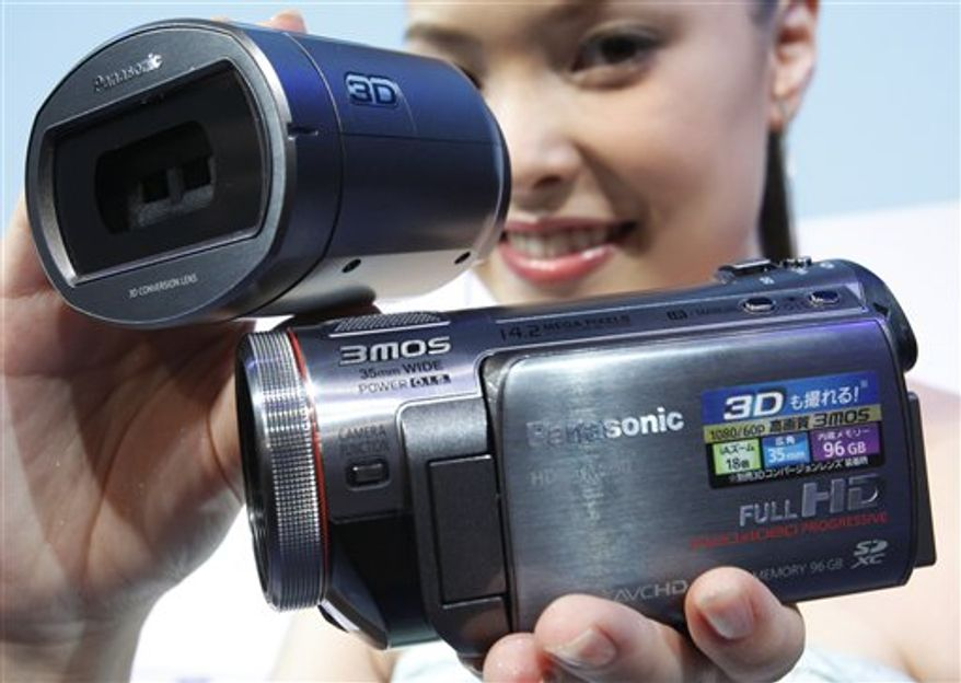 A model shows Panasonic's digital camcorder SDT750, right, capped with a 3-D conversion lens, during a press unveiling in Tokyo, Wednesday, July 28, 2010. The whole camcorder and lens setup starts at about 170,000 yen ($2,000), far more affordable than professional 3-D camcorders, which have been the only types available up to now for 3-D filming. The 3-D camcorders go on sale in Japan Aug. 20, and will be available in overseas markets later this year. (AP Photo/Shizuo Kambayashi)