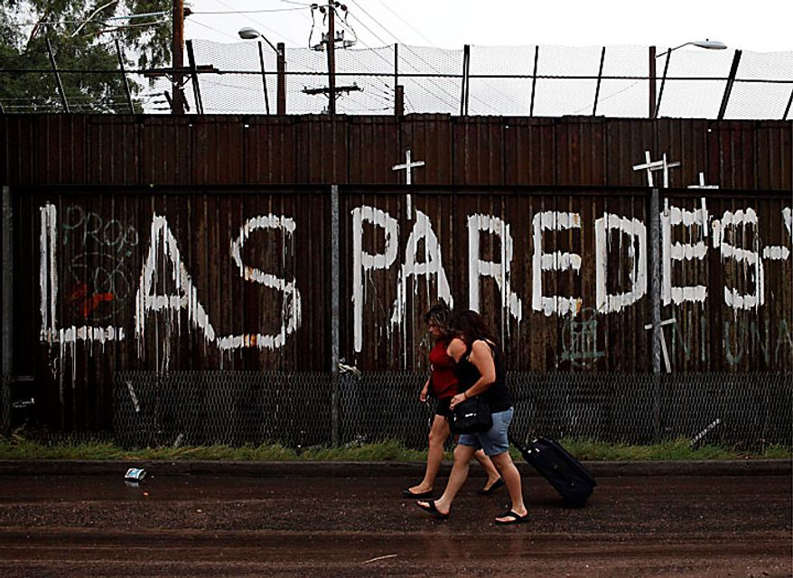 """Two woman walk along the U.S.-Mexico border showing graffiti that reads """"the walls"""" in Nogales, Sonora, Mexico, Tuesday, July 27, 2010. Arizona's new immigration law SB1070 takes effect Thursday, July 29. (AP Photo/Jae C. Hong)"""