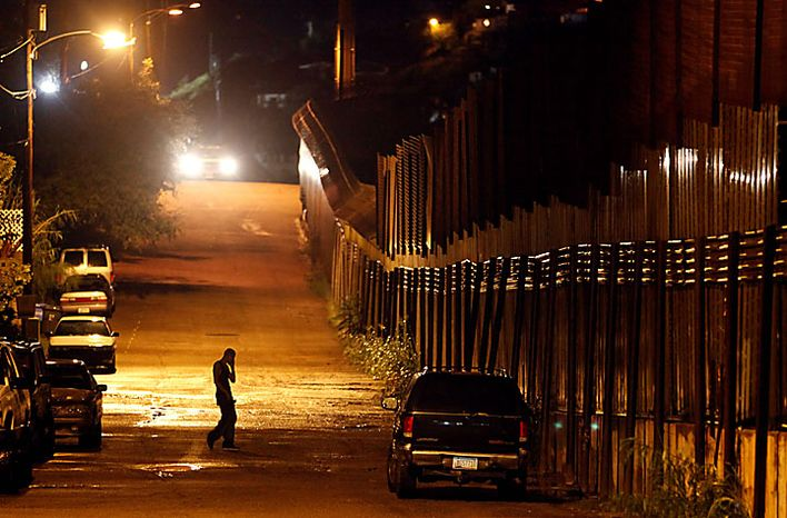 A man talks on the phone as he stands next to the U.S.-Mexico border in Nogales, Ariz., Tuesday, July 27, 2010. Arizona's new immigration law