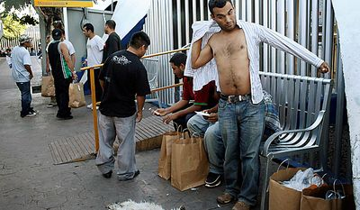 Jose Luis, right, an illegal immigrant who was deported to Mexico, gets dressed as he and other deportees gather near the Nogales Port of Entry in Nogales, Sonora, Mexico, Wednesday, July 28, 2010. A report by a think tank released Wednesday, Sept. 1, 2010, says global warming will increase illegal migration into the United States across the Mexican border. (AP Photo/Jae C. Hong)