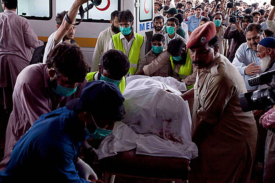 Volunteers push the dead body of a passenger on a stretcher at a local hospital in Islamabad, Pakistan on Wednesday, July 28, 2010. The passenger jet carrying 152 people crashed into the hills surrounding Pakistan's capital amid rain Wednesday, officials said. (AP Photo/Naveed Ali)